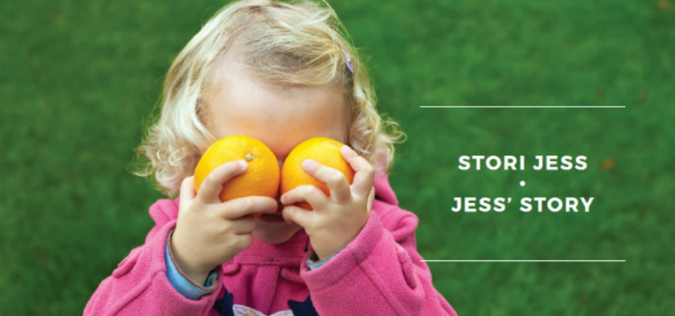 A toddler playfully holding up two oranges to her eyes