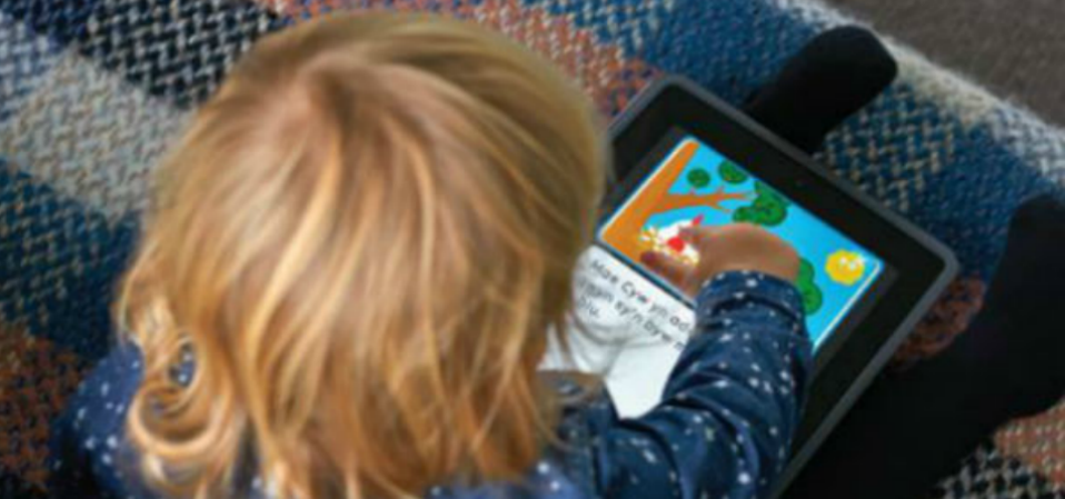 A toddler playing on an ipad
