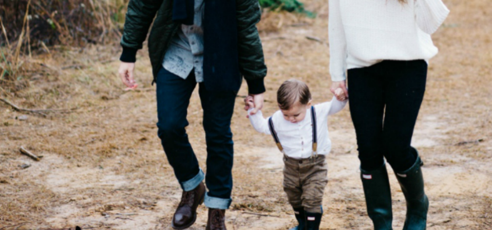 A mother and father holding hands with a toddler on a muddy walk