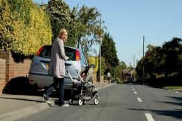 Photo of person pushing baby buggy into road as car parked on pavement