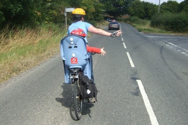 Photo of cyclist with child behind in seat. Cyclist and child passenger are indicating right turn with their arms (photo courtesy of Sustrans)